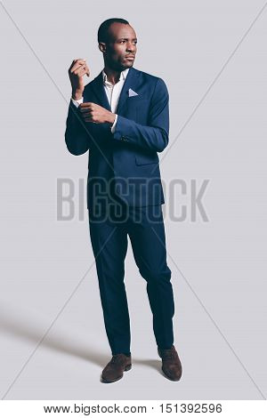 Used to look perfect. Full length of handsome young African man in full suit adjusting his sleeve and looking away while standing against grey background