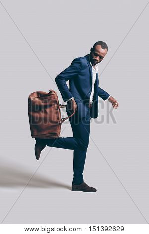 Playing with style. Full length of handsome young African man in full suit carrying brown leather bag on his foot while standing against grey background