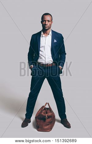Me and my bag. Full length of handsome young African man in full suit holding hands in pockets and looking at camera while standing against grey background with brown leather bag laying near him