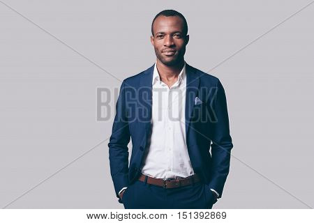 Young and handsome. Handsome young African man in smart casual jacket holding hands in pockets and looking at camera while standing against grey background