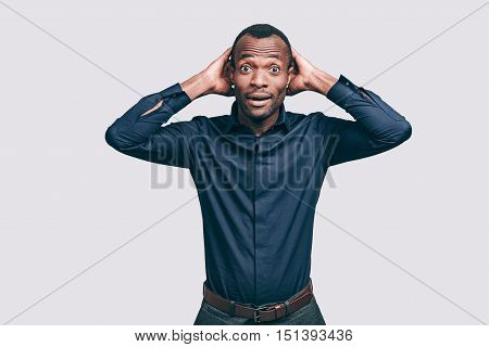 Feeling surprised. Surprised young African man holding hands behind head and looking at camera while standing against grey background