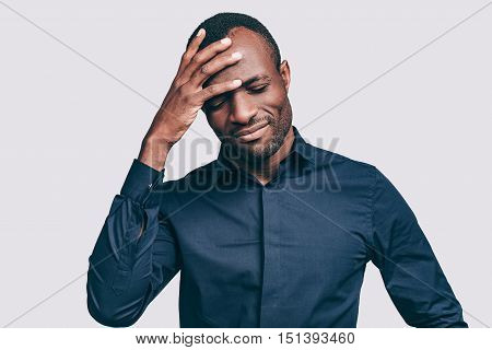 Feeling upset. Frustrated young African man touching head with hand and keeping eyes closed while standing against grey background