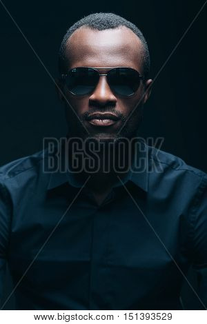 Cool and handsome. Portrait of handsome young African man looking at camera while being in front of black background