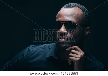 Cool and trendy. Portrait of handsome young African man  holding hand on chin and looking away while being in front of black background