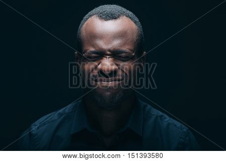 Feeling despaired. Portrait of young African man making a face while keeping eyes closed and being in front of black background