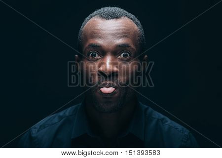 Feeling playful. Portrait of cheerful young African man sticking out tongue and looking at camera with smile while being in front of black background