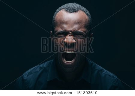 Feeling so angry! Portrait of furious young African man looking at camera and shouting while being in front of black background