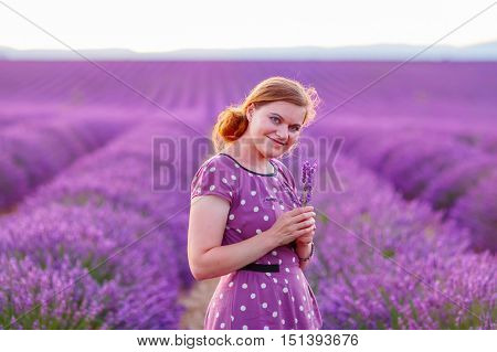 Romantic woman in lavender fields, having vacations in Provence, France. Girl traveling through Valensole plateau.