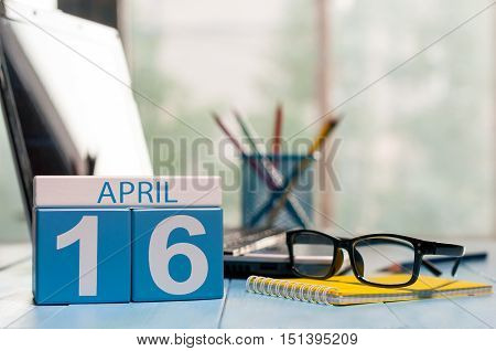 April 16th. Day 16 of month, calendar on business office background, workplace with laptop and glasses. Spring time, empty space for text.