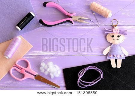 Set for children activity and creativity. Felt doll, scissors, thread, needles, pins, pliers, suede cord, felt sheets on wooden background with empty space for text. Children crafts