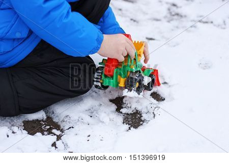 The part of the image of a small child who sits among the first snow and sand and plays with a red toy construction vehicles. Visible hand dressed in a blue jacket black pants and boots.