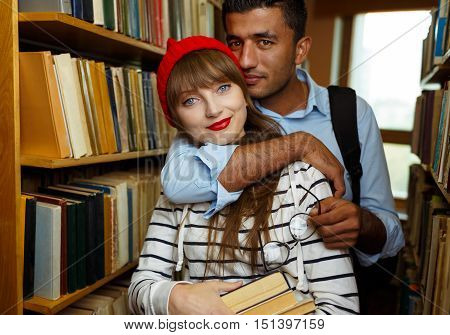 Young student couple choosing books between the shelves in the library