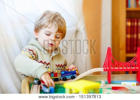 Little toddler boy playing with wooden railway, indoors. Blond funny kid having fun with toys and learning.