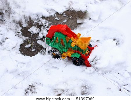 Walks in the fresh air. A small bright toy car bulldozer (excavator) is located on the first fallen snow on a cloudy day.