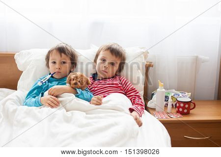Two Sick Boys, Brothers, Lying Down In Bed With Fever