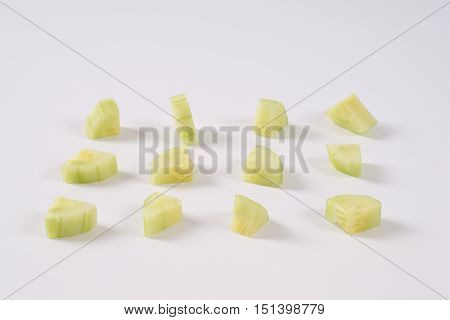 pieces of fresh cucumber arranged on white background