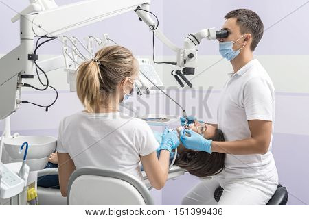 Woman in goggles on a dental chair and a dentist with assistant who sit next to her. Man looks on her teeth using a dental microscope and holds dental instruments. Blonde holds an air water syringe.