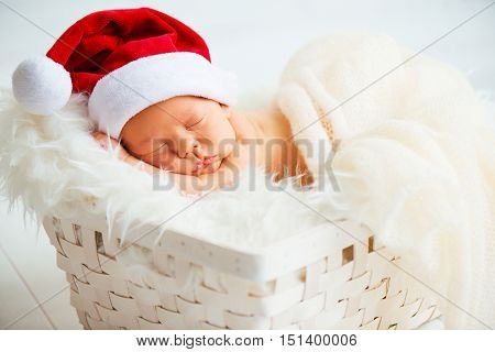 sleeper newborn baby in a Christmas Santa cap