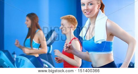 Group of people at the gym exercising on cross trainers .