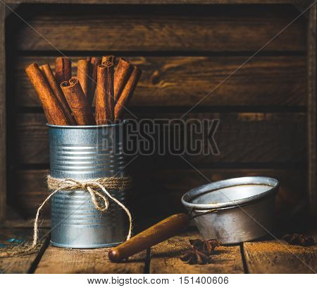 Cinnamon sticks in can tied with rope, anise stars and sieve on rustic wooden background, copy space