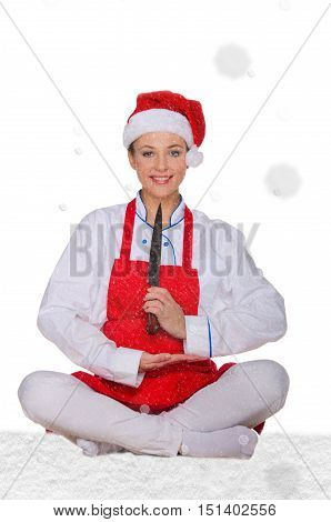 Cook in Santa Claus hat yoga knife under snow on white background