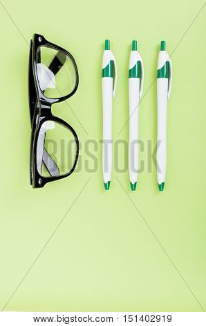 Top View Of Desktop With Spectacles And Pens