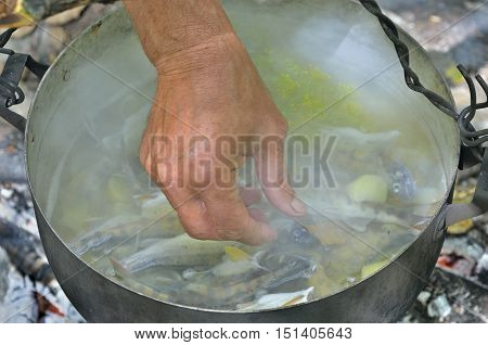 A cooking fish-soup in pot on bonfire.
