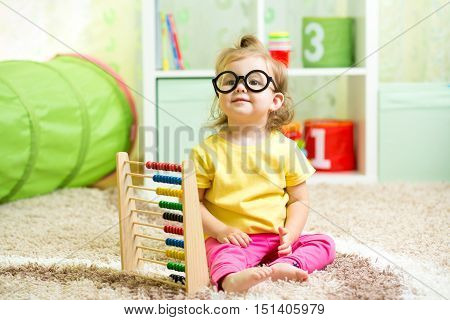 child kid weared glasses playing with abacus toy indoor