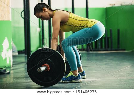 Young fit woman pulling up weight in the gym.