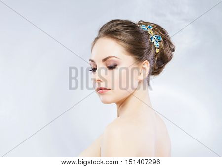 Gorgeous, young blond wearing sapphire crown over grey background.