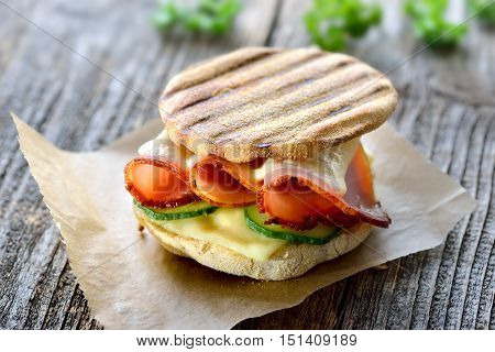 Grilled panini with ham, cheese and cucumber served on sandwich paper on a wooden table