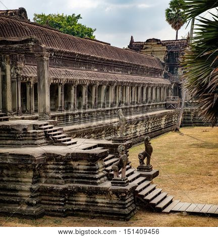 Ancient ruins of temple complex Angkor Wat surrounded by palm trees Siem Reap Cambodia.