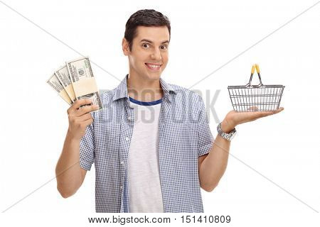 Happy guy holding a small empty shopping basket and bundles of money isolated on white background