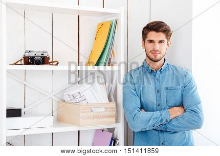 Smiling casual businessman with hands folded standing at office shelf with arms folded