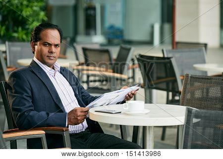 Unsmiling businessman with newspaper sitting in cafe