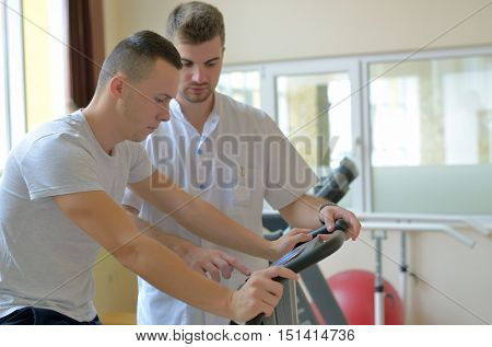 Young man on exercise bicycle in physiotherapy gym center