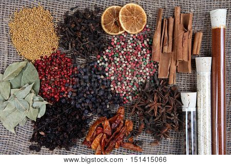 Different Spices On Sackcloth And Glass Tubes With Seasonings Background
