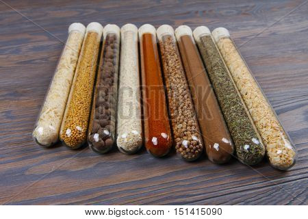 Set Of Spices In Glass Tubes On An Old Wooden Background