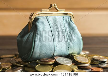 Purse for coins. Leather purse is on top of the coins.