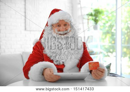 Santa Claus with credit card and tablet at home