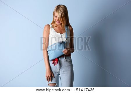 Young beautiful woman with leather clutch on light blue background