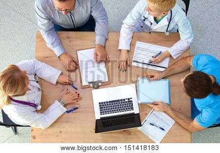 Attractive female doctor shaking a patient's hands in her office.