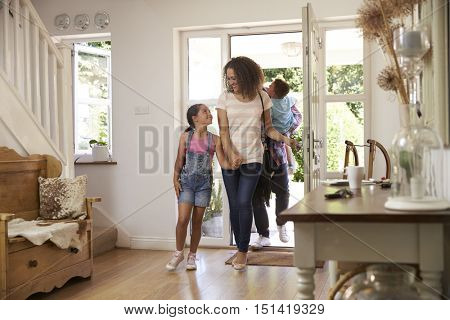 Family In Hallway Returning Home Together