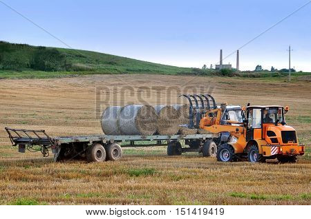 Grodno, Belarus - August 15, 2016: Agricultural field in Belarus. The process of collecting and handling haystacks using two harvesting machines.