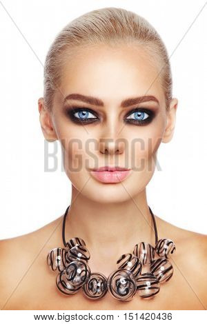 Close-up portrait of young beautiful woman with stylish smoky eye make-up and fancy glass necklace over white background