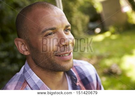 Head And Shoulders Shot Of Mid Adult Man Sitting On Swing