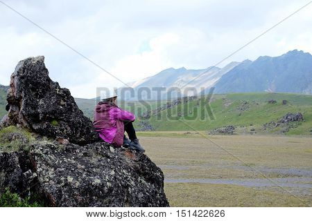 Girl On A Cliff Overlooking The Mountains