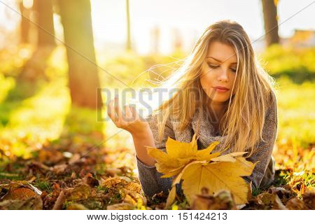 Beautiful young blonde Caucasian woman lying in park in leaves, relaxing on sunny autumn day, holding leaves. Back lit, natural lighting, vibrant colors.