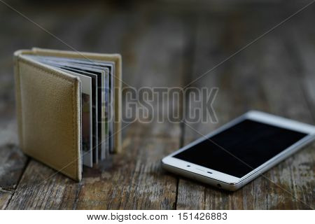 Smartphone And Photo Book Lying On The Wooden Background.