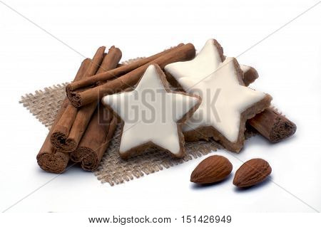 Cinnamon stars with almonds and cinnamon sticks isolated on white